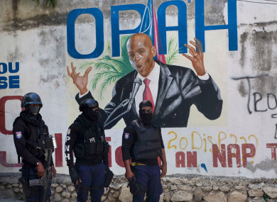 Police stand near a mural featuring Haitian President Jovenel Moise, near the leader's residence where he was killed by gunmen.