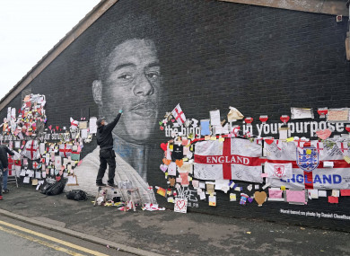 Street artist Akse repairs the mural of Manchester United striker and England player Marcus Rashford.