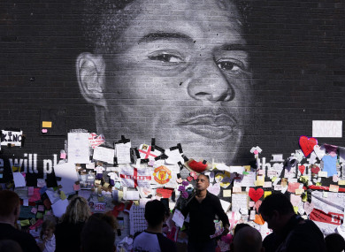 People gather to view the messages of support at the mural of Marcus Rashford