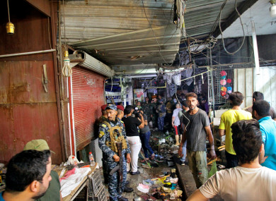 People at the site of a bombing in Wahailat market in Sadr City, Baghdad.