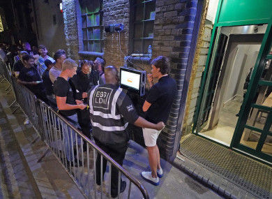 People have their ID checked as they queue up for the Egg nightclub in London