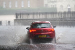 A car drives through flood water in Horse Guards Road in central London