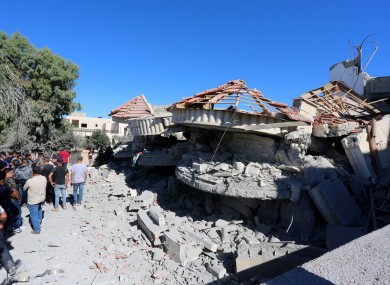 Palestinians inspect the rubble of the house of Palestinian-American Muntasser Shalaby,