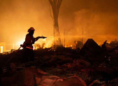 A fire crew member extinguishes the remains of a building that burned down in Greenville, CA
