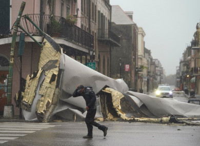 A man passes by a section of roof blown off of a building in the French Quarter by Hurricane Ida winds in New Orleans, US.