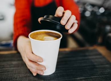 File photo of a barista and a disposable coffee cup