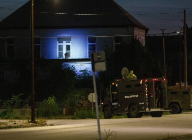 Illinois State Police in armoured trucks shine a spotlight on a building during a manhunt after a shooting in southern Illinois