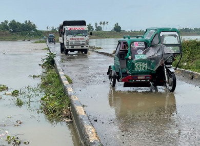 Motorists cross a bridge as the river starts to swell due to approaching typhoon Chanthu in Cauayan, northern Philippines.