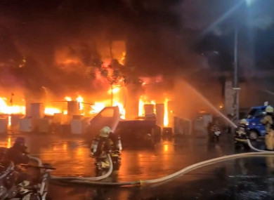 In this image taken from video by Taiwan's EBC, firefighters battle a blaze at a building in Kaohsiung, in southern Taiwan
