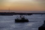 A fishing trawler leaves a harbour